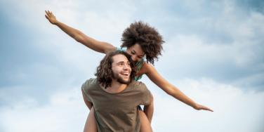 woman getting piggyback ride flying like airplane