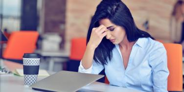 woman stressed head on hand in front of laptop