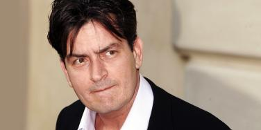 photo of Charlie Sheen in a suit and loose collar looking sideways at camera