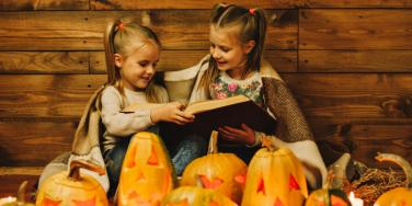 2 girls reading a book on halloween