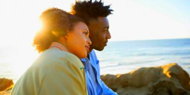 lovely couple with brown skin stares out at the ocean, backlit