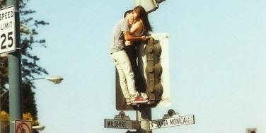 couple kissing street sign
