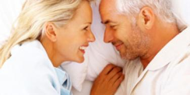 older couple laughing in bed