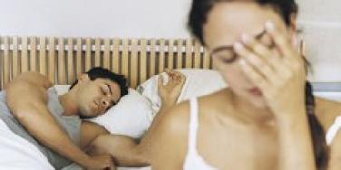 couple in bed man asleep woman with head in hand