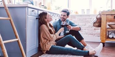 man and woman sitting on the floor of a kitchen drinking wine
