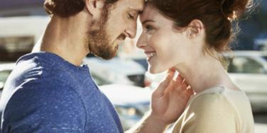 a white man with a short beard stares lovingly in the eyes of a white woman, with brown hair in a bun
