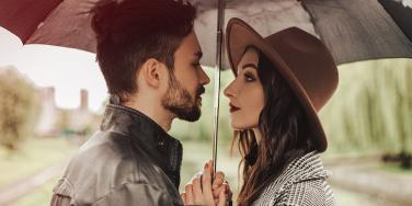 man and woman standing under umbrella looking at each other