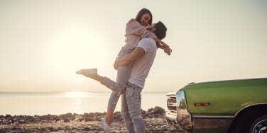 man and woman at beach next to car