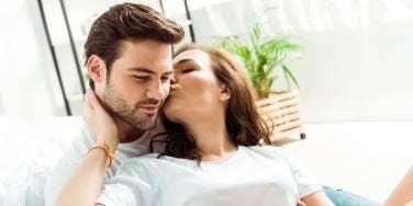 woman kissing man's ear