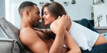 woman and man about to kiss on the couch