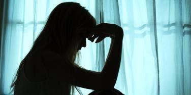 dark silhouette of woman by a window