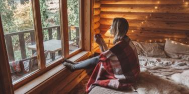 woman wrapped in blanket looking out the window