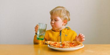 toddler in a yellow shirt eating pizza.