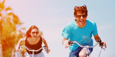 happy man and woman riding bikes