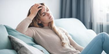 emotionally exhausted woman sitting on couch