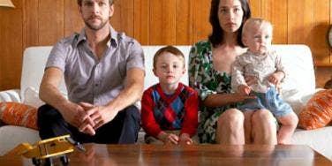 serious family sitting on sofa