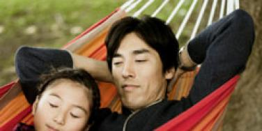 father and daughter napping in a hammock