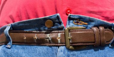 closeup of unbuttoned jeans with a fastened belt