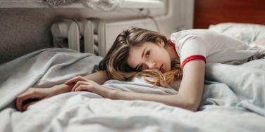 woman lying down in bed feeling sick
