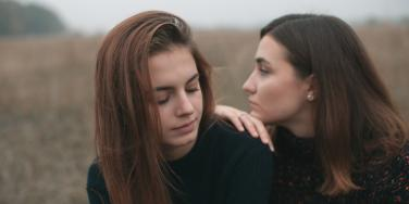 woman leaning on another woman friendship
