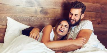 man and woman cuddling in bed