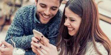 couple laughing playing on phone together
