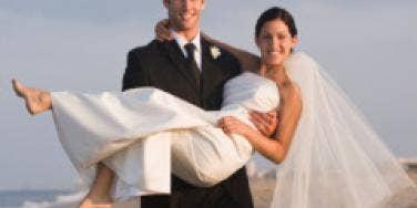 groom holding bride on the beach