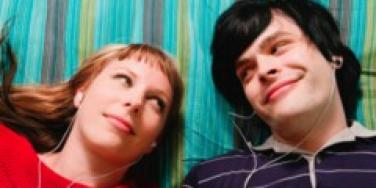 guy and girl laying on blanket listing to headphones