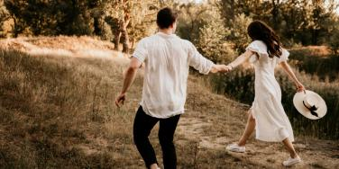 woman and man running in field
