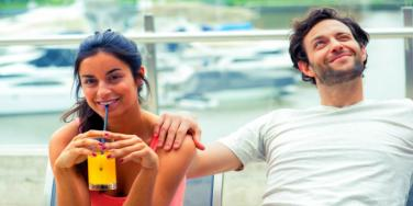 girl smiling sipping drink next to guy