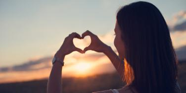 woman making a heart in the sunset