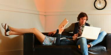 man and women reading together on the couch
