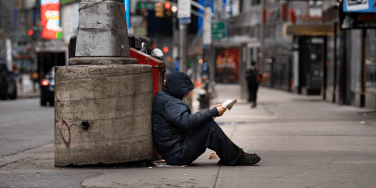 Homeless man reading a book on the street