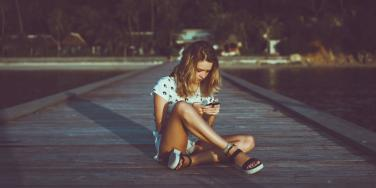 girl sitting on the ground texting