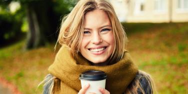 smiling woman in scarf drinking coffee