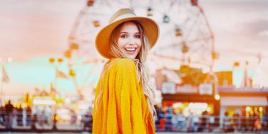 happy woman with a ferris wheel behind her