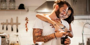 woman hugging man and looking over his shoulder at smartphone