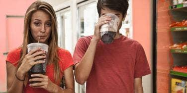 couple drinking large sodas