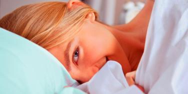 woman shyly smiling in bed