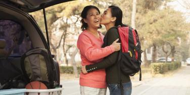young adult child going to college kissing mom on cheek