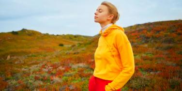 relaxed woman in yellow sweater outdoors