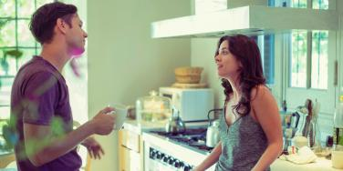 man and woman talking in the kitchen
