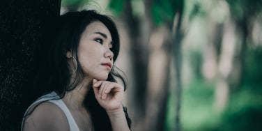 woman sad next to tree