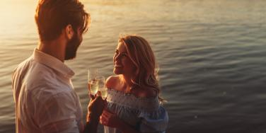 man and woman sharing a drink by the water