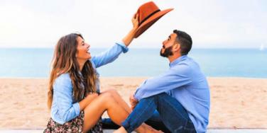 guy and girl smiling on the beach with a hat