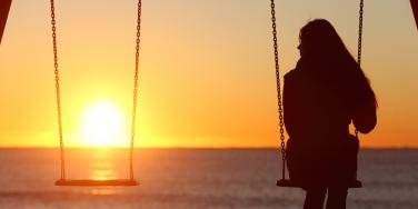 woman on swingset with sunset