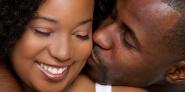 black man kissing smiling black woman on cheek