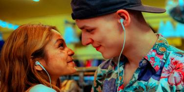 couple staring into each others eyes smiling listening to music