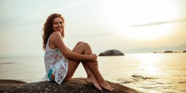 smiling woman sitting by the ocean at sunset