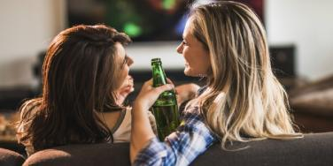 two women laughing with beers in hand
